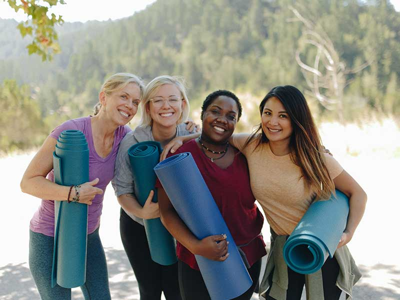 Individuals Smiling with Yoga Mats